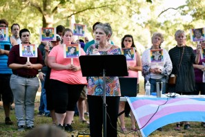 Brenda McWilliams, a founding member of East Texas PFLAG, is flanked by volunteers holding photos of people killed in the Orlando nightclub shooting as she thanks the crowd for attending a memorial vigil Thursday at Bergfeld Park in Tyler. Andrew D. Brosig/Tyler Morning Telegraph