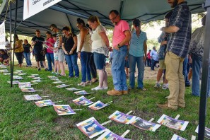 Diverse members from around the community and around the area view photos of the 49 people killed in the Orlando nightclub shooting following a memorial vigil Thursday at Bergfeld Park in Tyler. The names of the deceased and a brief biography of each was read during the emotional service. Andrew D. Brosig/Tyler Morning Telegraph